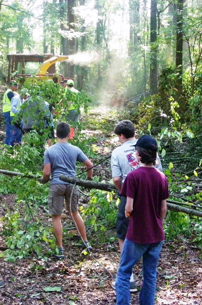 Volunteers from the Boy Scouts of America drag downed brush to a chipper operated by NPS staff.