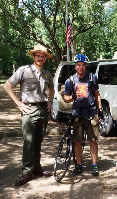 Park Ranger Jake Dinkelaker with bicyclist at the Mount Locust Visitor Center in Natchez, Mississippi.